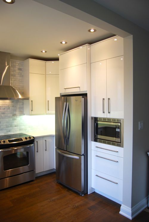 A modern custom kitchen with high gloss warm white cupboard doors in Toronto